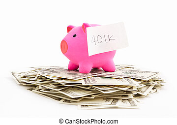 Pink piggy bank with sticker writeen 401K over pile of dollar bills