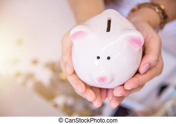 Piggy bank a container for saving money, Piggy bank in hand, money savings concept