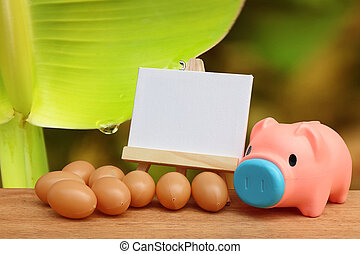 piggy bank and canvas frame with drop from banana stem background