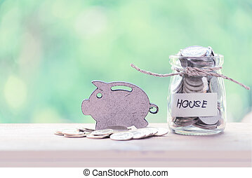 Piggy bank and golden coins on wood table with pastel background, saving money concept