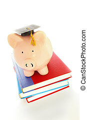 piggy bank and graduation cap on books - student debt concept