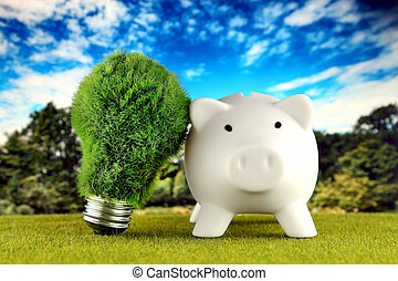 Piggy bank and green eco light bulb with grass and blue sky background. Renewable energy. Electricity prices, energy saving in the household.