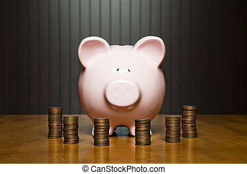 piggy bank and money - Piggy bank on a table surrounded by...