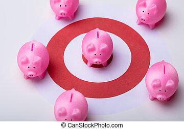 Piggy Bank And Red Darts Target On Desk - Pink Piggy Banks ...