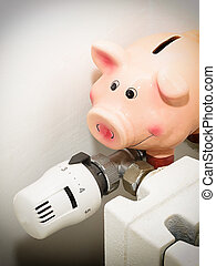 Piggy bank and the valve on the radiator for energy savings