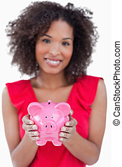 Piggy bank being held by a brunette woman