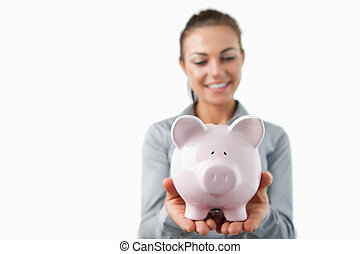 Piggy bank being held by female bank assistant