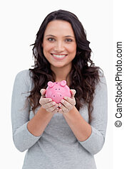 Piggy bank being held by smiling woman