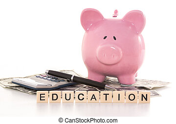 Piggy bank beside calculator and education spelled out in...