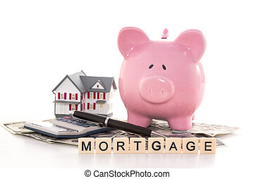 Piggy bank beside calculator miniature house and mortgage...