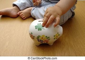 Piggy bank - child putting a coin in a piggy bank