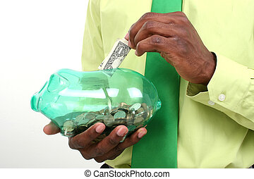 Piggy Bank - Close up of man putting a dollar in a piggy...