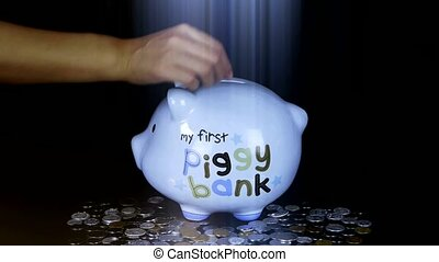 Piggy bank coin drop in black space, Piggy Bank Savings RMB and rays lights.