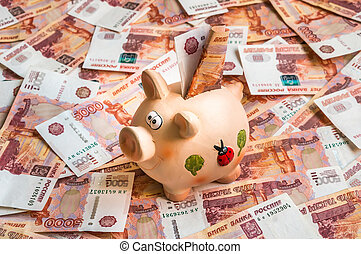 Piggy bank in a pile of russian five thousand banknotes,...