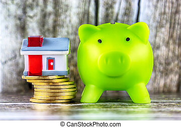 Piggy bank, miniature house and golden coins on wooden background. Savings in the household.