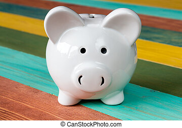 Piggy-bank on color wooden background