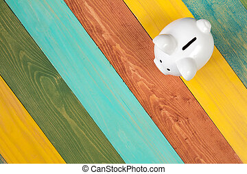 Piggy bank on color wooden background