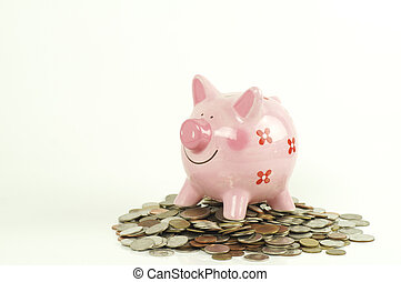 piggy bank on pile of money coin isolated on white background