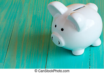 Piggy bank on the blue wooden surface