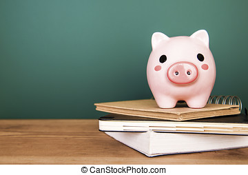 Piggy bank on top of books with chalkboard, cost of education theme