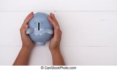 Piggy bank, savings concept - Someones hand holding and...