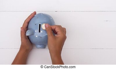 Piggy bank, savings concept - Someones hand putting coin and...