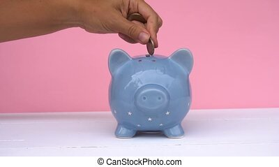Piggy bank, savings concept - Someones hand putting coin...