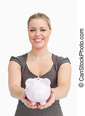 Piggy bank showing by a pretty woman