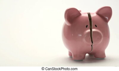 Piggy bank splitting in two halves with cash inside on white background