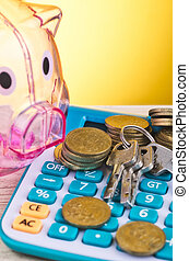 piggy bank, stacking coins, bunch of key and calculator on wooden desk for home loans concept
