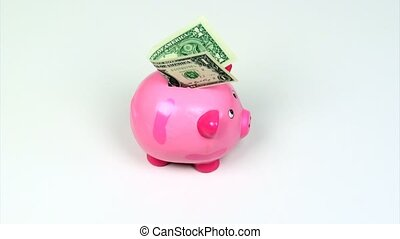 Piggy bank - Pink piggy bank with dollar bill on a rotating...