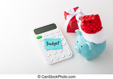 Piggy bank wearing christmas hat with budget on word on calculator