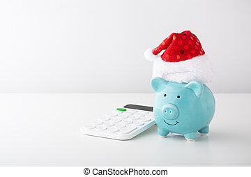 Piggy bank wearing christmas hat with calculator