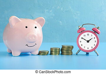 piggy bank , wekker, en, stapel muntstukken, gefotografeerde, close-up., vrolijk, keramisch, varken, op, een, blauwe , achtergrond.