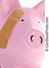 Piggy bank with a bandage closeup. Healthcare costs