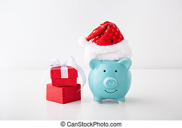 Piggy bank with christmas hat and gift box