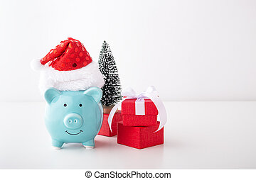 Piggy bank with christmas hat, gift and decor on white background
