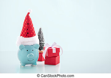 Piggy bank with christmas hat on blue background