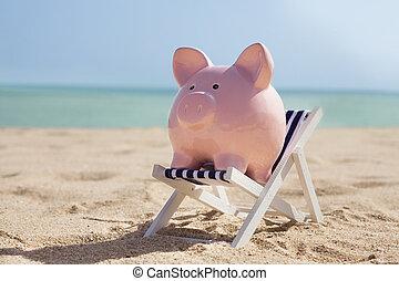 Piggy Bank With Deckchair On Sandy Beach