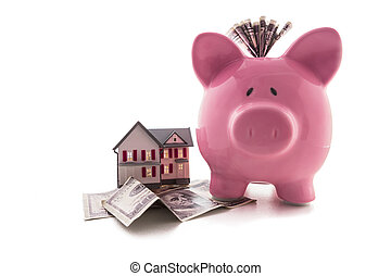 Piggy bank with dollars beside miniature house model