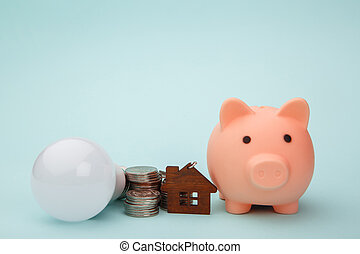 Piggy bank with money banknote,led light bulb and house figure. Power saving concept