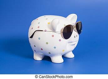 Piggy bank with sunglasses on blue background
