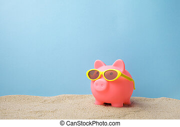 Piggy bank with sunglasses on the beach