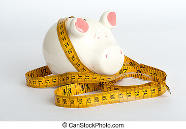 Piggy bank with tape measure on white, side view