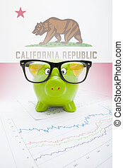 Piggy bank with US state flag on background - California