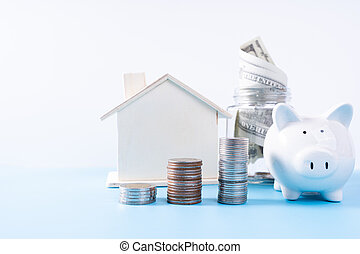 Piggy bank with wooden house and stack coins and money paper inside jar isolated grey background. Property investment and house mortgage financial concept.