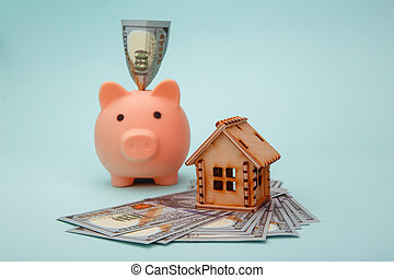 Piggy bank with wooden model of house and money banknotes on blue background. Savings money for buy house