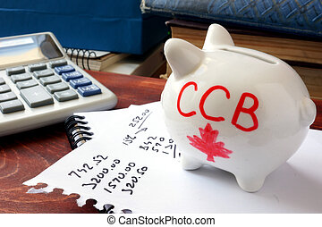 Canada child benefit concept. - Piggy bank with word CCB....