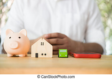 Piggy bank, wood home, toy car and smart phone place on wood table against man background.