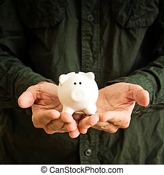 Piggy coin bank in cupped hands of man.